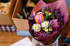 Gentille femme même de fleuriste tenant un beau bouquet de floraison coloré de fleur de pivoine, oeillets, roses, eustoma images libres de droits
