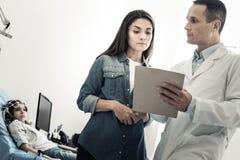 Gentille femme sérieuse regardant les notes de docteur Photo libre de droits