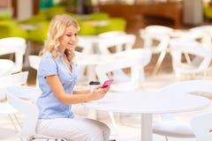 Gentille femme s'asseyant dans le café Images libres de droits