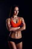 Gentille femme sexy de forme physique montrant des muscles abdominaux d'isolement au-dessus du fond noir Corps féminin qualifié Photo stock