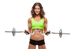 Gentille femme sexy faisant la séance d'entraînement avec la grande haltère (retouchée) Photos stock