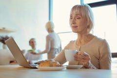 Gentille femme supérieure tenant une tasse de café Images libres de droits