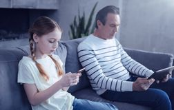 Gentille fille agréable regardant son écran de smartphone photographie stock libre de droits