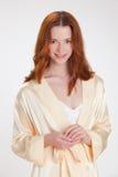 Gentille fille dans la robe de chambre à la maison beige Photos stock