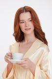 Gentille fille dans la robe de chambre à la maison beige Image libre de droits