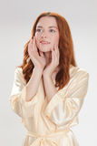 Gentille fille dans la robe de chambre à la maison beige Image stock