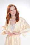 Gentille fille dans la robe de chambre à la maison beige Photographie stock