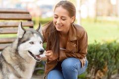 Gentille fille jouant avec le chien Photo stock