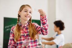 Gentille fille joyeuse tenant une glissière de microscope photographie stock libre de droits