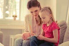 Gentille fille mignonne dessinant une image dans son carnet photos stock
