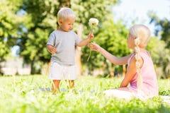 Gentille fille obtenant une fleur d'un petit frère images stock