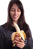 Gentille fille regardant une banane Images stock