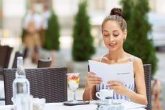 Gentille fille s'asseyant dans le café Photos libres de droits