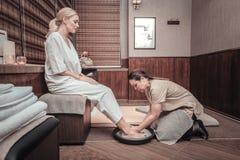 Gentille jeune femme faisant un bain des pieds photographie stock libre de droits