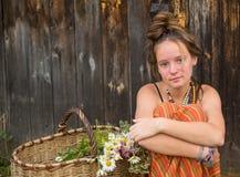 Gentille jeune fille dans un arrangement rural avec un panier des fleurs sauvages nature Photographie stock