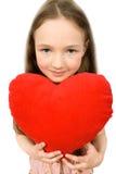 Gentille petite fille avec le jouet mou de coeur d'isolement Photographie stock