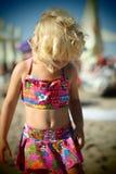 Gentille petite fille blonde habillée sur la plage pendant l'été regardant vers le bas Images stock