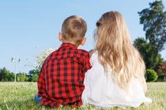 Gentille petite fille et garçon s'asseyant vers l'arrière Image stock