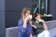 Gentilles femmes buvant du café au café et au repos Image libre de droits