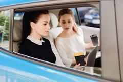 Gentilles femmes d'affaires travaillantes dures travaillant dans la voiture Image libre de droits
