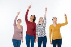 Gentilles femmes joyeuses se tenant sur le fond blanc Photographie stock libre de droits