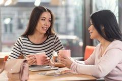 Gentilles femmes positives se réunissant dans le café Photographie stock