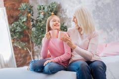 Gentilles grand-mère joyeuse et petite-fille encourageant avec des tasses Image libre de droits