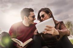 Gentils amis de couples détendant se reposer sur le pré Photographie stock libre de droits