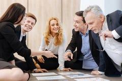 Gentils collègues heureux s'asseyant en cercle Image libre de droits