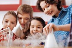 Gentils enfants gais visitant un laboratoire scientifique Image libre de droits