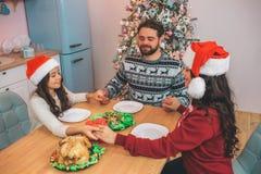 Gentils et délicieux membres de famille s'asseyant à la table et au jeu Ils tiennent les mains de chacun et maintiennent des yeux photographie stock libre de droits