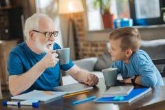 Gentils grand-père avec plaisir et petit-fils ayant le thé Photographie stock