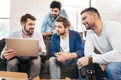 Gentils hommes agréables regardant l'écran d'ordinateur portable Image stock