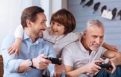 Gentils hommes avec plaisir tenant des consoles de jeu Images stock