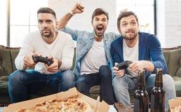 Gentils hommes beaux jouant des jeux vidéo Photos libres de droits