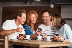 Gentils hommes et femmes à l'aide des téléphones Photos stock