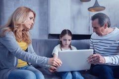 Gentils parents de soin s'asseyant autour de sa fille image libre de droits