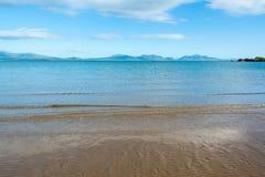 Gentle волны на песчаном пляже Anglesey и гор Snowdonia - 2 Стоковое Изображение