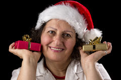 Gentle Aged Woman Holging Two Small Gifts. Venerable middle-aged woman with a Kris Kringle hat cracking a smile. She is holding a small Xmas present in each hand Stock Photos