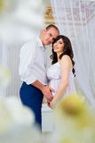 Gentle beautiful pregnant couple near tulle curtains Stock Photo