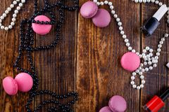 Gentle biscuits macaroons on a wooden background with the attributes of a cosmetic bag. stock images