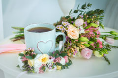 Gentle bouquet of flowers and blue mug with heart. On a table Stock Photo
