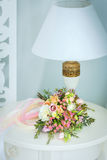 Gentle bouquet of flowers and lamp. Gentle bouquet of flowers lies on a table near a lamp Stock Photography