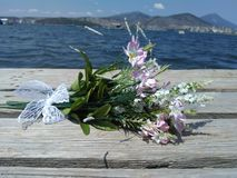 Gentle bouquet of small flowers on the background of the sea. Close-up of a small bouquet drawn by a lace ribbon on a wooden sea pier Stock Photography