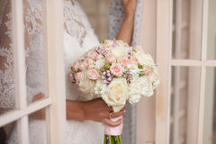 Gentle bridal bouquet in hands. Bridal bouquet of pink color in hands Royalty Free Stock Photo