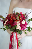 Gentle bridal bouquet in hands. Bridal bouquet of red color in hands Stock Image