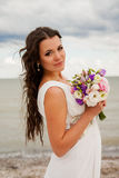 Gentle bride with a bouquet on the beach. Stock Image