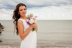 Gentle bride with a bouquet on the beach. Royalty Free Stock Images