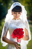 The gentle bride with a red bouquet Stock Images