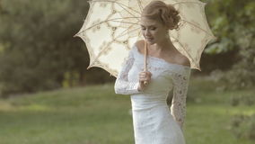 Gentle bride with an umbrella on the nature stock footage